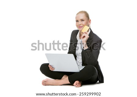 blonde businesswoman seated on the floor holding credit card  - stock photo