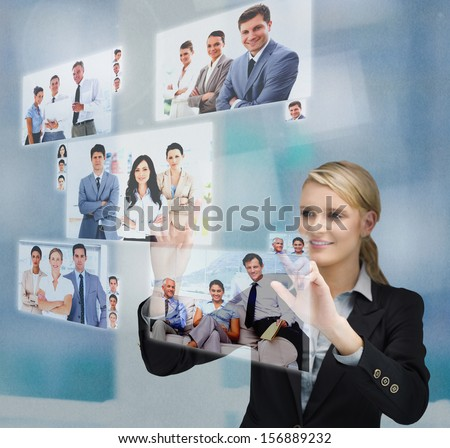 Blonde businesswoman selecting image from digital interface showing coworkers