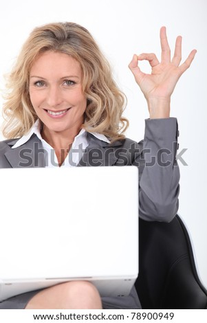 Blonde businesswoman with a laptop giving the OK sign - stock photo