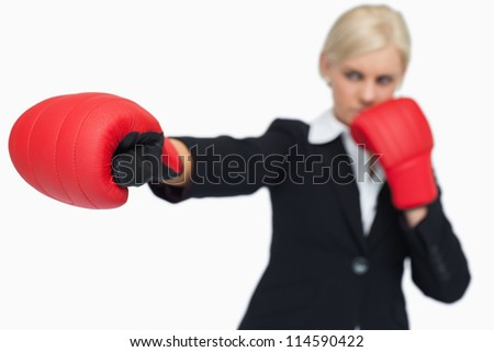Blonde businesswoman with red gloves boxing against white background