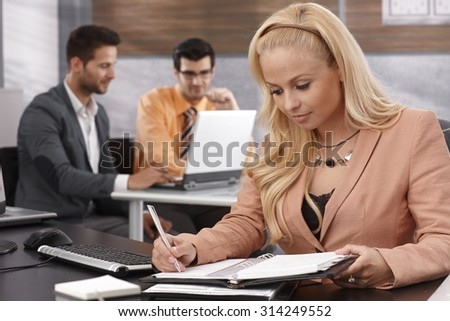Blonde businesswoman working at desk in office. - stock photo