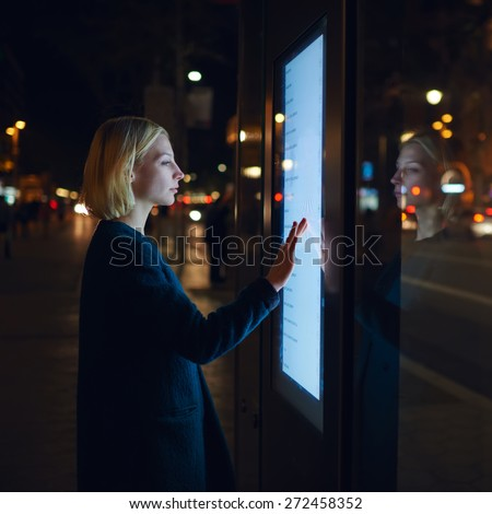 Blonde caucasian businesswoman touching sensitive screen of smart city bus stop in night city with out-of-focus lights, young female doing internet money payment with automated teller machine - stock photo
