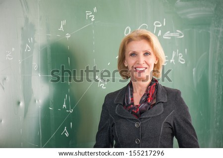 Blonde caucasian female teacher posing on a blackboard - stock photo