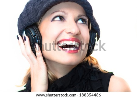 Blonde caucasian girl listening to the music with a pair of headphones - stock photo
