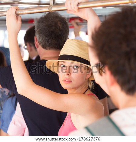 Blonde caucasian lady traveling by public transport. Lonely in the crowd. - stock photo
