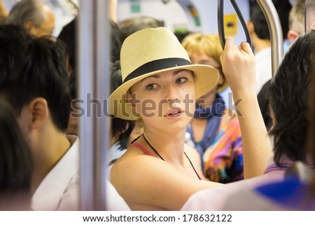 Blonde caucasian lady traveling by public transport. Lonely in the crowd.