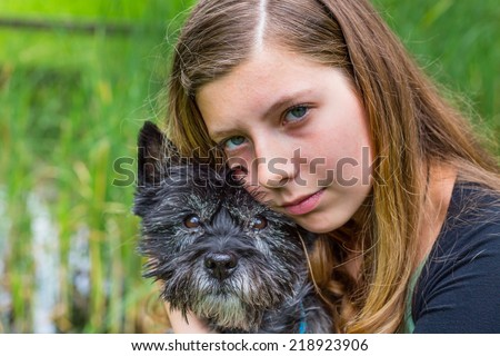 Blonde caucasian teenage girl embracing and hugging black dog in nature with green reed in background - stock photo