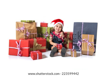 Blonde christmas kid around several presents pointing to the front