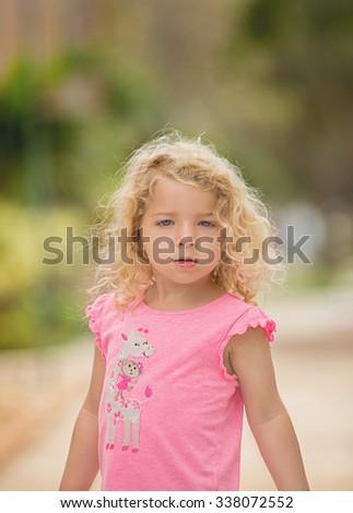 Blonde curly hair blue-eyed toddler - stock photo
