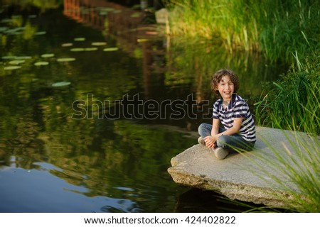 Blonde curly-haired boy sitting on the edge of the pond