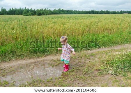 Blonde curly preschooler girl is playing on farm dirt road near puddle - stock photo