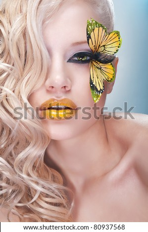 Blonde curly woman with yellow butterfly on lashes - stock photo
