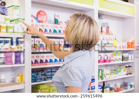 Blonde customer pointing medicine from shelf in the pharmacy - stock photo