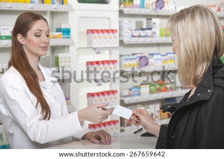 Blonde customer shows her credit card to the pharmacist