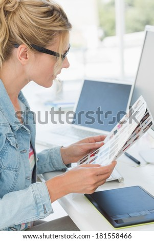 Blonde editor looking over contact sheet at her desk in creative office