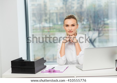 blonde elegant woman sitting behind her desk at work with laptop - stock photo