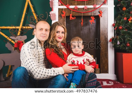 blonde family of Europeans Russian family for Christmas New Year near the fireplace and green Christmas tree, smiling family, holiday, , son smiling, husband, wife and son, happy family in sweaters
