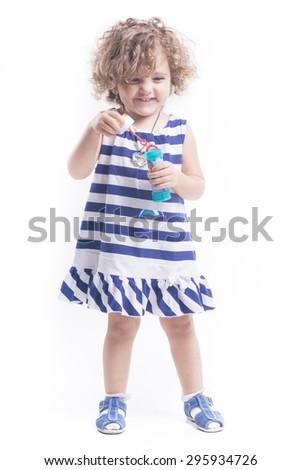 Blonde female child with soap bubbles and blue dress - stock photo