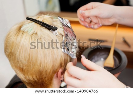 blonde female having some new highlights at hair salon - stock photo