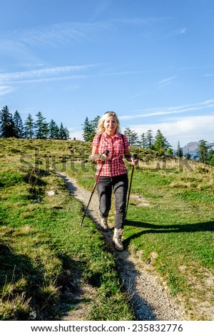 blonde female hiker in a summer landscape - stock photo