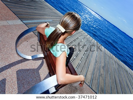 blonde female relaxing in a futuristic chair and enjoying the view to the seaside with sun reflexion - stock photo