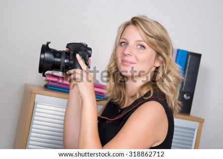 Blonde female with a professionnal camera at office - stock photo