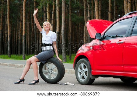 Blonde girl asks for help on the road near her broken car - stock photo