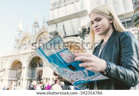 Blonde girl checking the map in Venice, st. Mark square  - stock photo