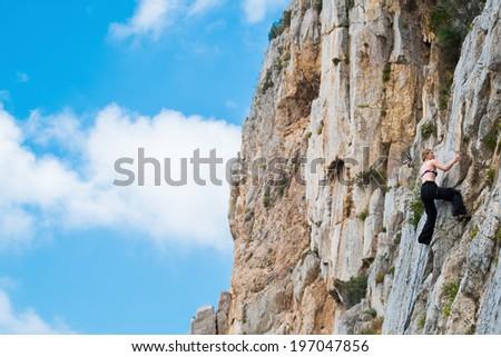Blonde girl climbing in bikini in Masua, Sardinia, Italy - stock photo