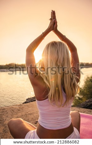 Blonde girl doing yoga by the river sunset - stock photo