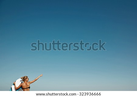 Blonde girl dressed in swimsuit standing on the ocean ready to surfing, female surfer holding surfboard. sky copy-space. - stock photo