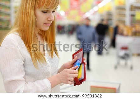 Blonde girl get	credit card from purse in store; shallow depth of field - stock photo