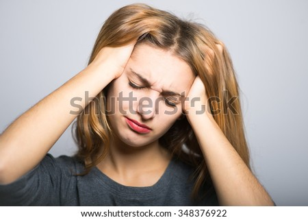 blonde girl has a severe headache, with clean skin, lifestyle concept studio photo isolated on a gray background