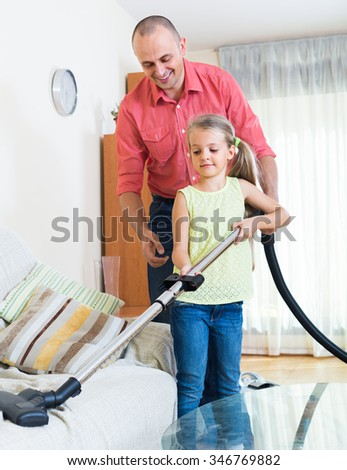 blonde girl helping father to do regular clean-up in  living- room