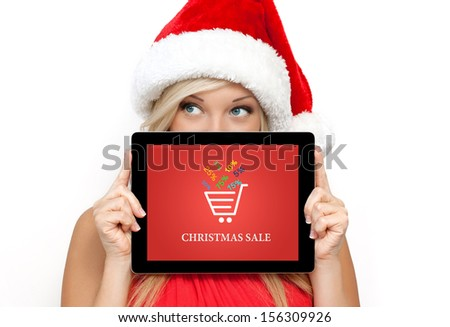 blonde girl in a red Christmas hat on New Year, holding tablet computer with christmas sale on a screen - stock photo