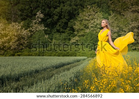 Blonde girl in a yellow light dress is on the field with yellow flowers. Her hair fluttering. - stock photo