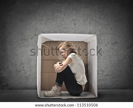 Blonde girl in jeans and white t-shirt crouched in a box