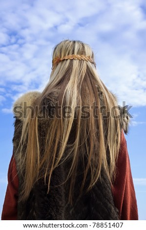 Blonde girl in the Scandinavian suit on a blue sky background - stock photo