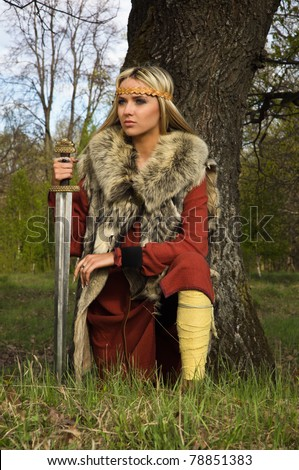 blonde girl in the Scandinavian suit with sword - stock photo