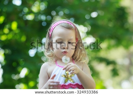 Blonde girl is blowing on white Taraxacum officinale or common dandelion seeds in her arm - stock photo