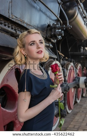 Blonde girl is waiting for the locomotive rose retro old train station - stock photo