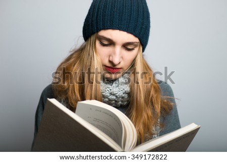 blonde girl leafing through the book, Christmas and New Year concept, studio photo isolated on a gray background - stock photo