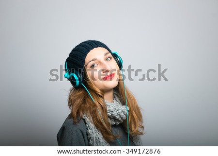 blonde girl listening to music on headphones, Christmas and New Year concept, studio photo isolated on a gray background