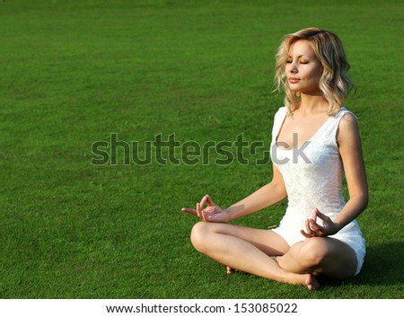 Blonde girl meditating on green grass. Beautiful young woman seating in Yoga pose of lotus in the park. Outdoors - stock photo