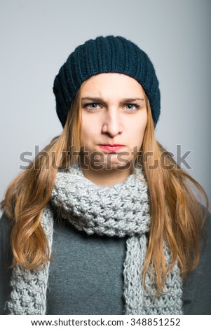blonde girl offended, dressed in winter clothing, Christmas and New Year concept, studio photo isolated on a gray background
