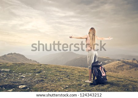 Blonde girl opening her arm on a mountain - stock photo