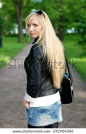 Blonde girl outdoor in park with a sports bag and sun glasses