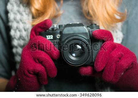 blonde girl photographed in vintage camera, Christmas and New Year concept, studio photo isolated on a gray background - stock photo