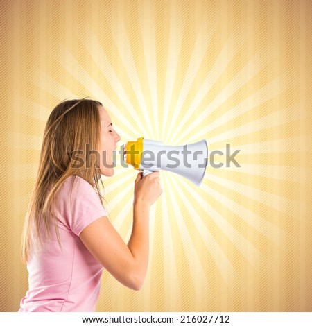Blonde girl shouting with a megaphone over pop background  - stock photo