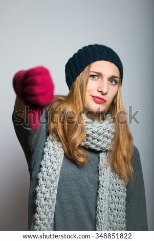 blonde girl shows that she does not like it, dressed in winter clothing, Christmas and New Year concept, studio photo isolated on a gray background